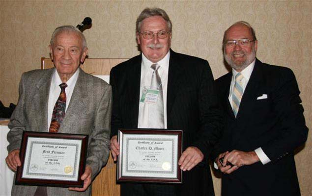 Fred Freeman (left) and Charles Moore (centre) receiving Fellow of the Canadian Numismatic Association Awards from Tim Henderson