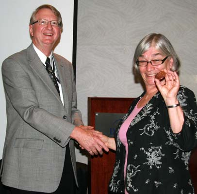 C.P.M.S. President Cliff Beattie presents Geraldine Chimirri-Russell with a medal for giving a presentation on mythological themes of 19th century vignettes at the luncheon