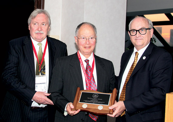 Dr. Marvin Kay (centre) accepting the Paul Fiooca Award from Charles Moore and Dan Gosling