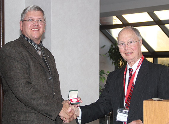 Stephen Woodland (left) receiving from Dr. Marvin Kay the Guy Potter Literary Award for 2011